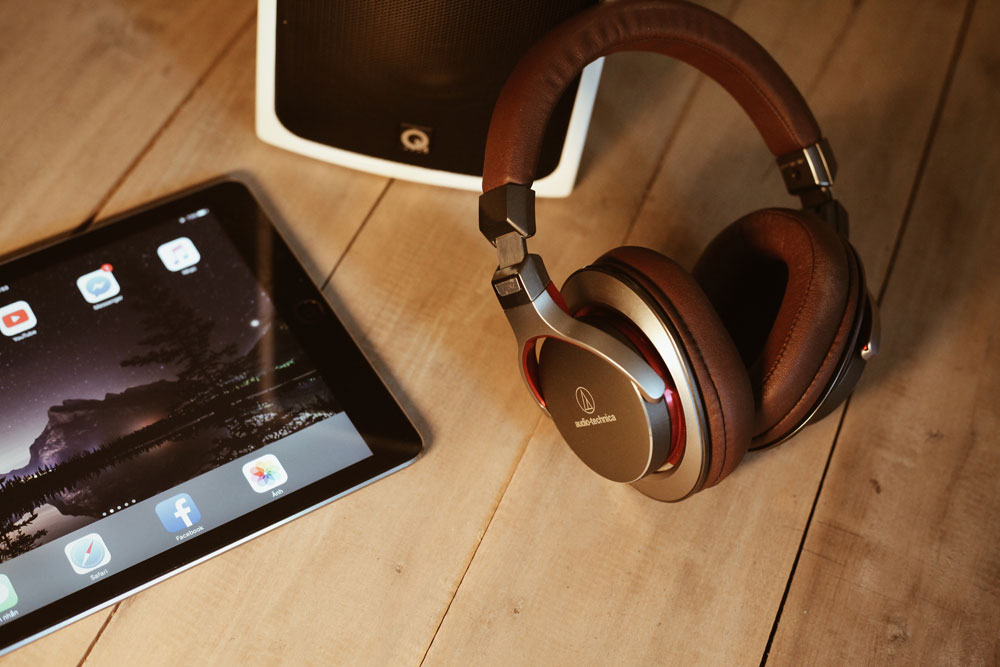 A pair of modern wireless Audio Technica headphones next to an iPad